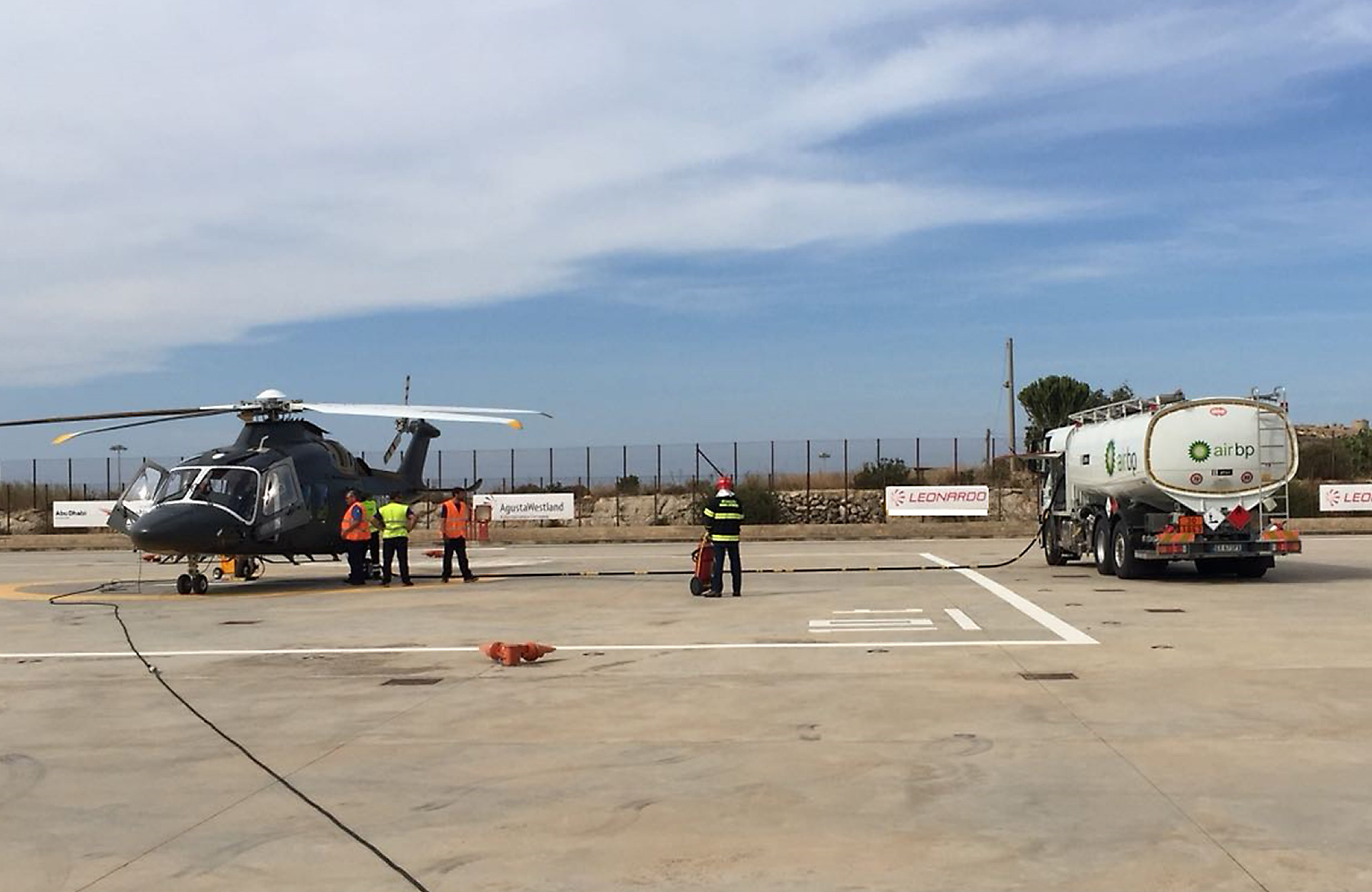 Operators refuelling a helicopter and Air BP tanker