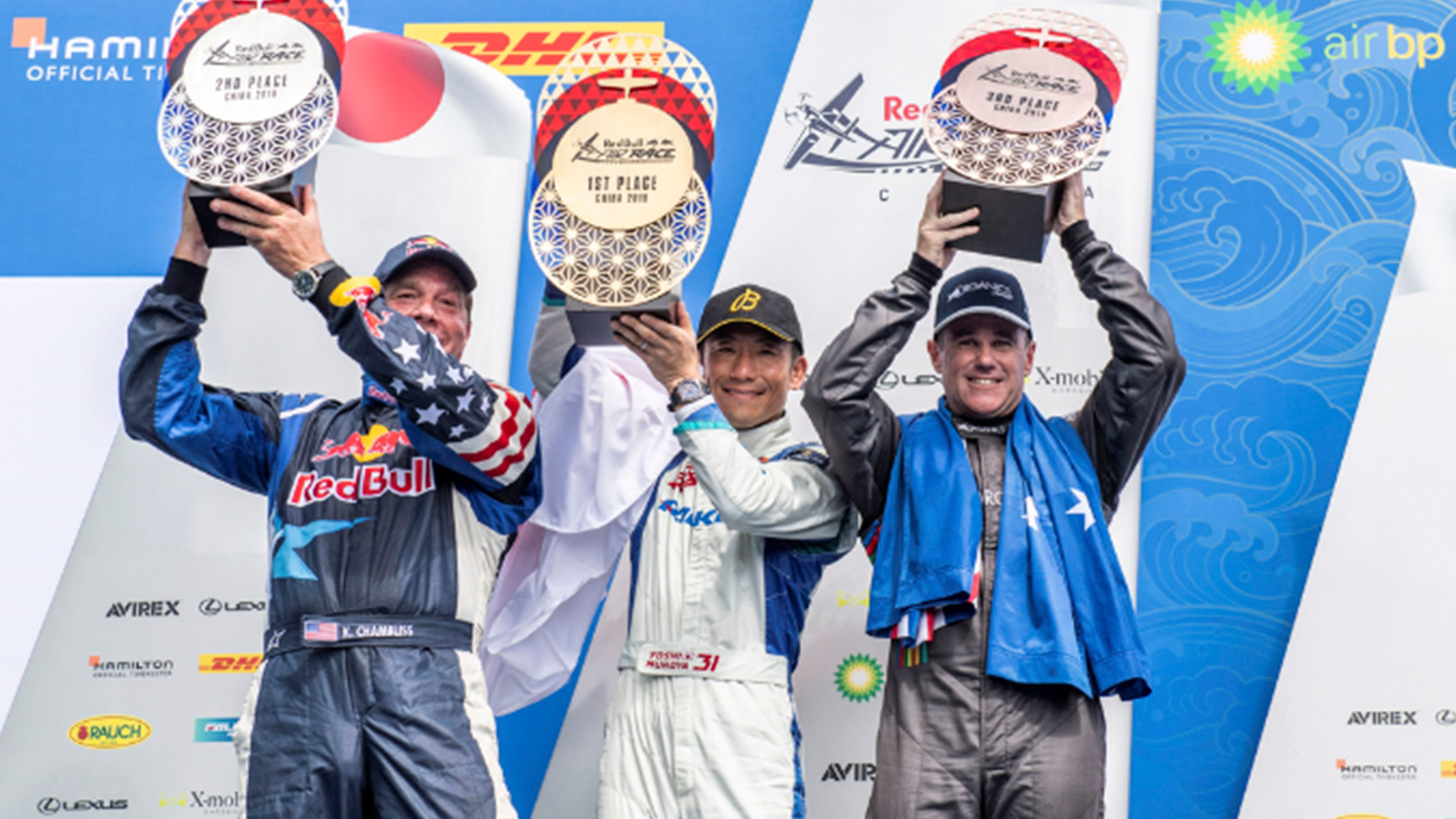 Red Bull Air Race podium with three pilots holding trophies
