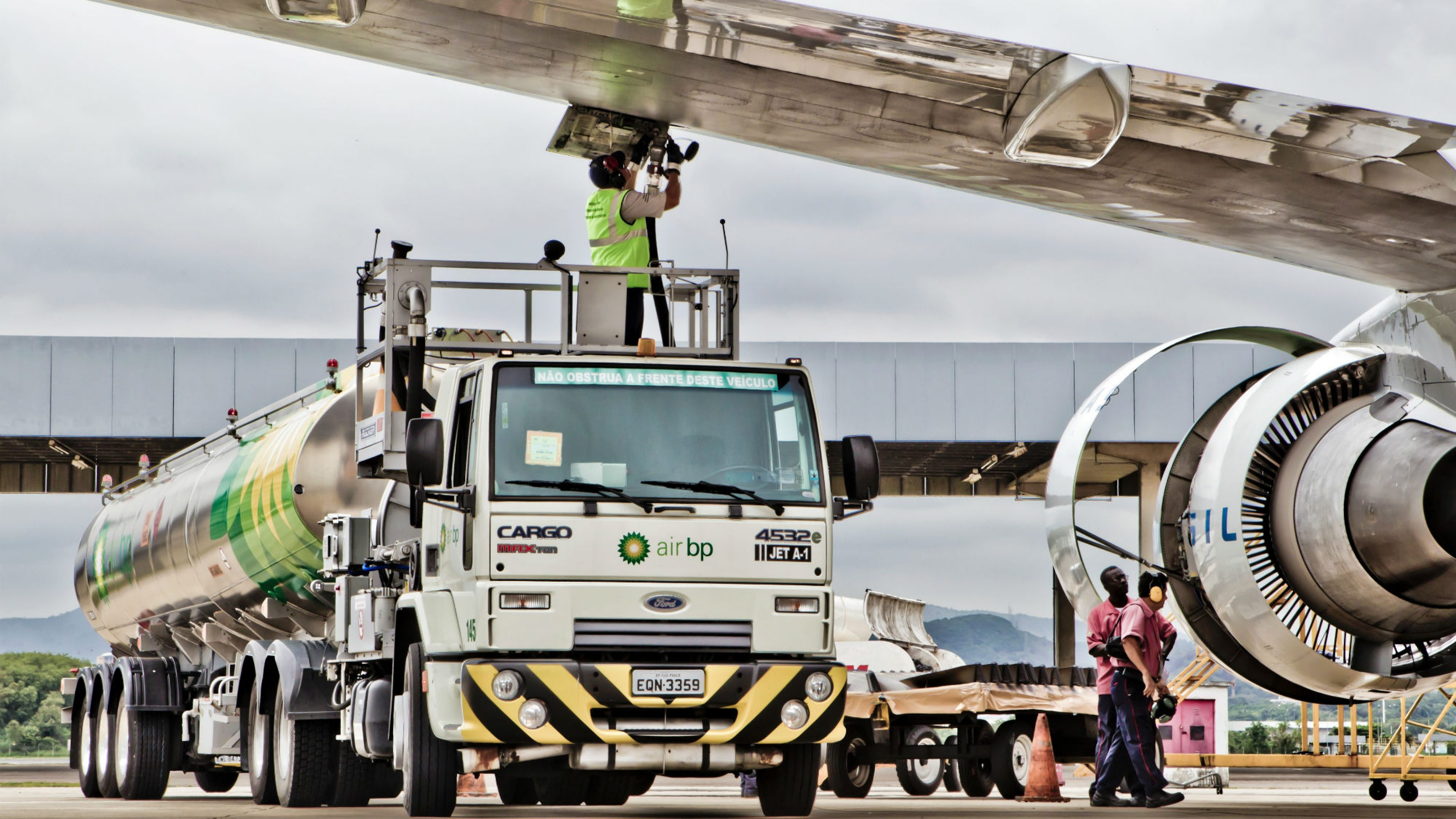 An Air BP tanker driver under the wing of an A320 aircraft at Galeao Airport in Rio de Janeiro, Brazil
