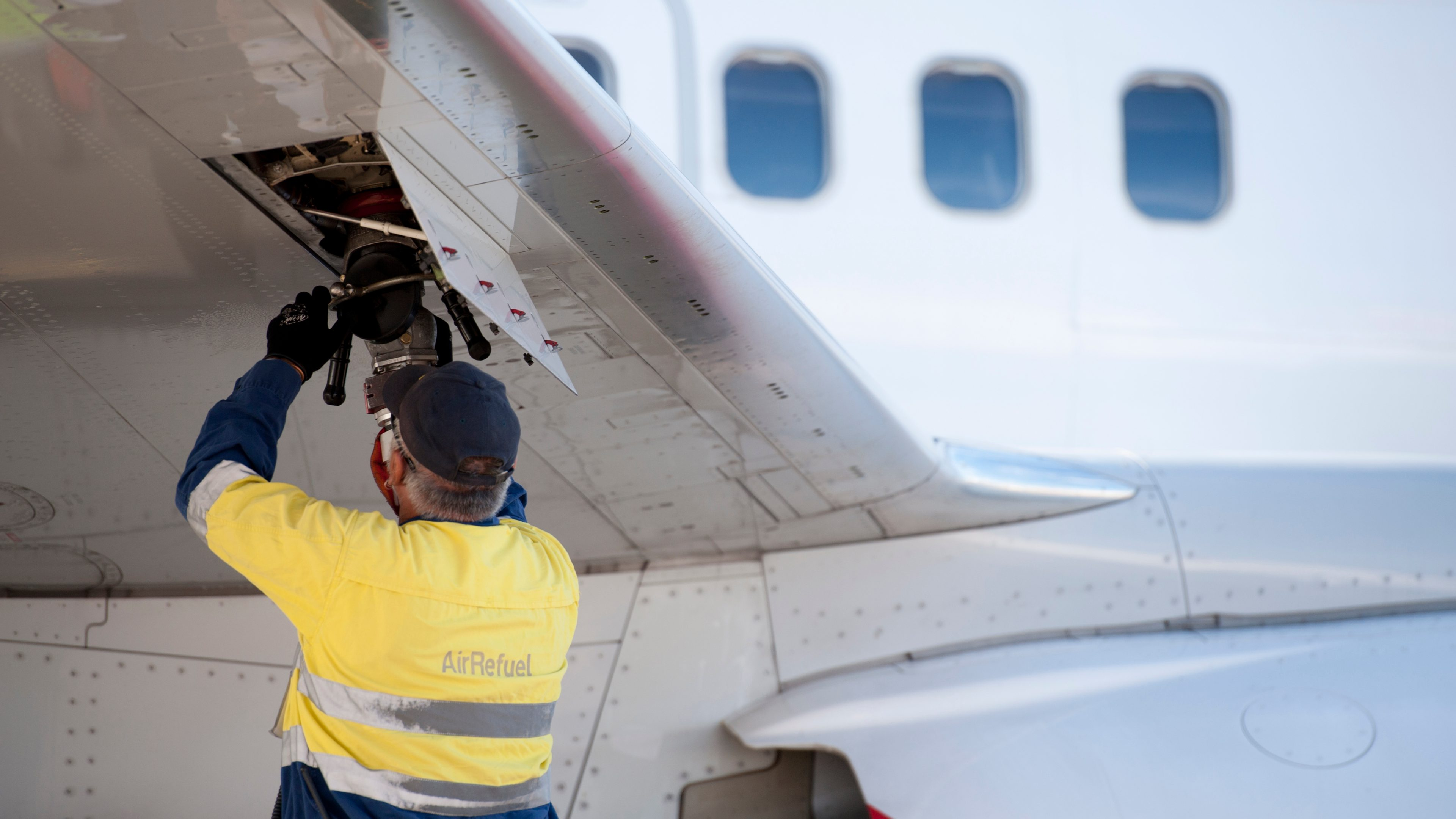 Kelvin Knights connecting the aviation fuel hose to commence under wing refuel of an aircraft at Brisbane Airport, Australia.