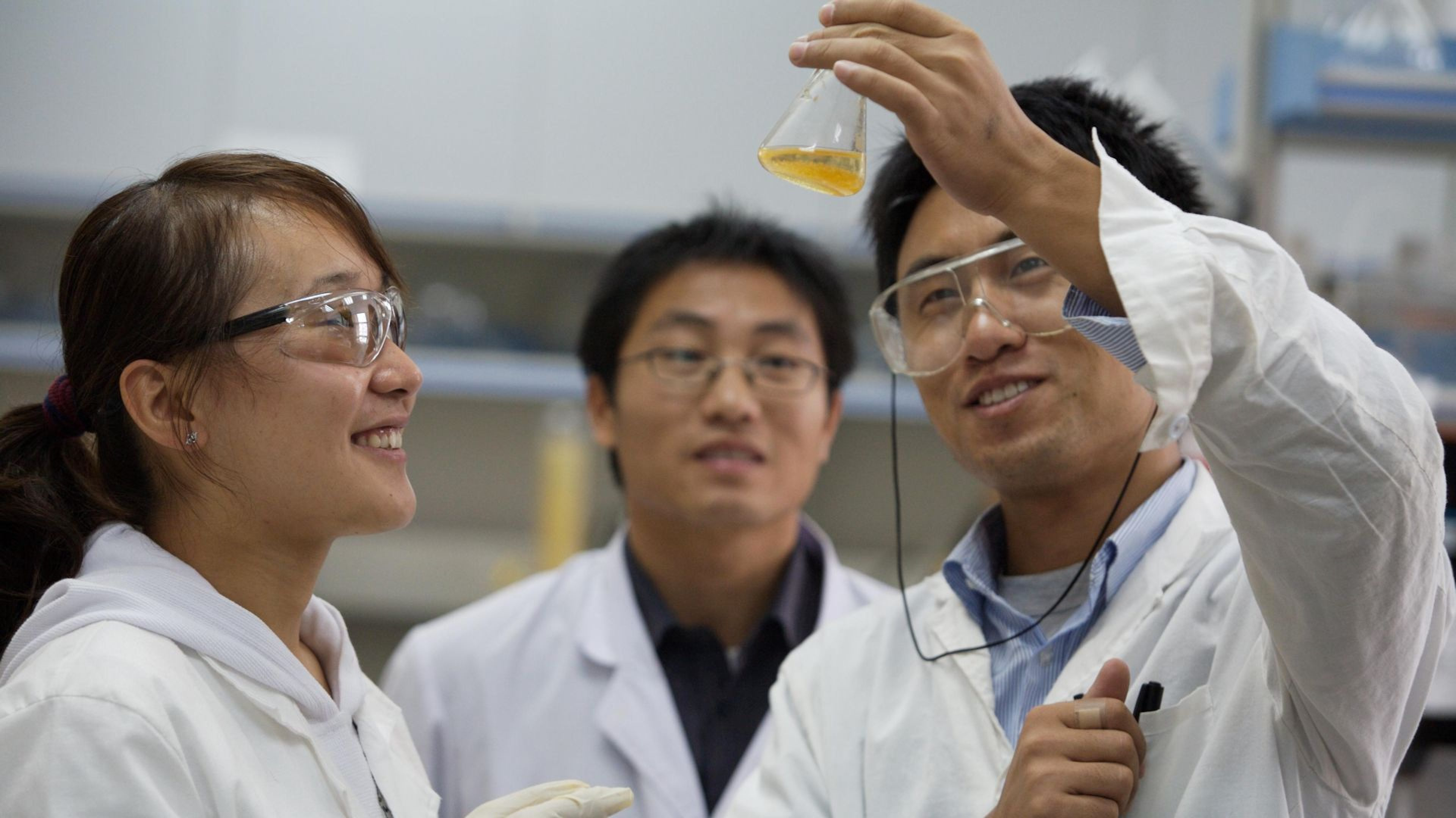 Researchers discussing the contents of a beaker in the laboratory of the Dalian Institute of Chemical Physics (DICP) in Dalian, China.