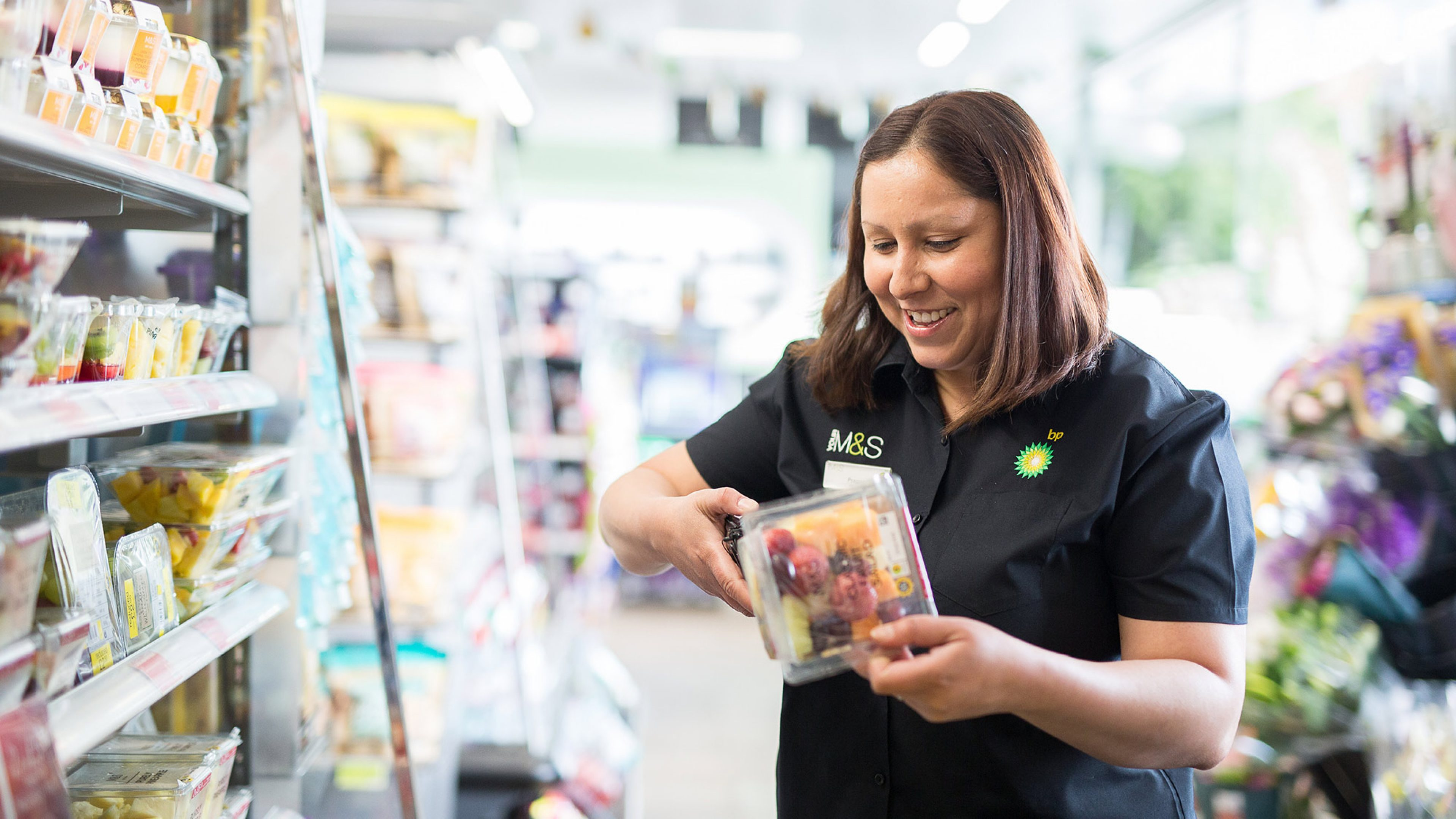 An employee from  BP Marks and Spencer  refilling the fridge in the store located at a UK service station