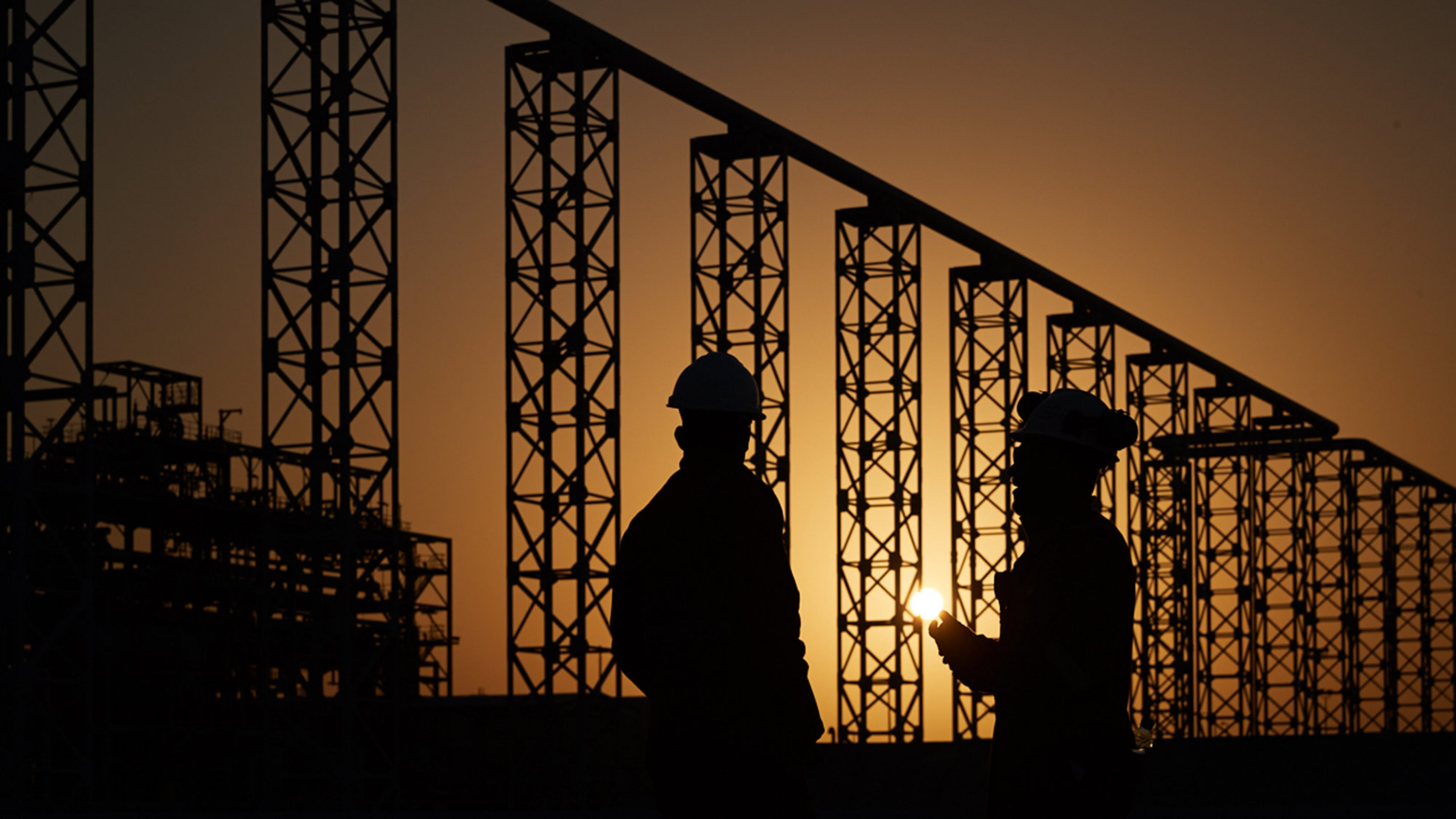 BPs Khazzan project with two workers in silhouette at sunset