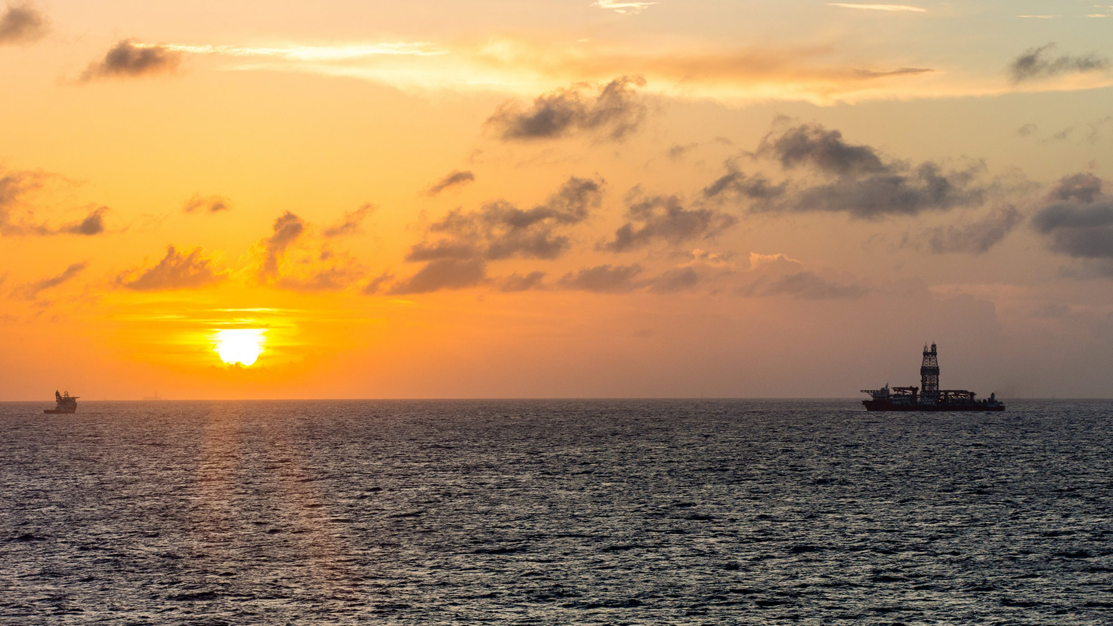 A drill ship and supply vessel in the Gulf of Mexico at sunset