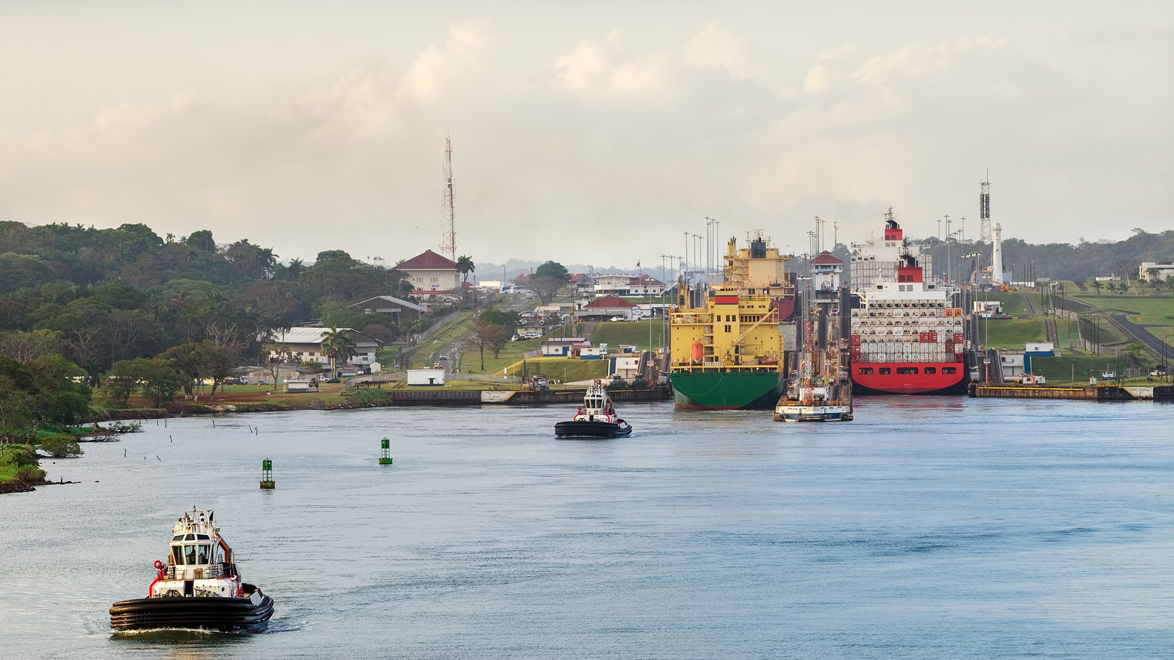 Cargo ships enter the Miraflores lock on the Panama Canal. Image courtesy of Adobe Stock