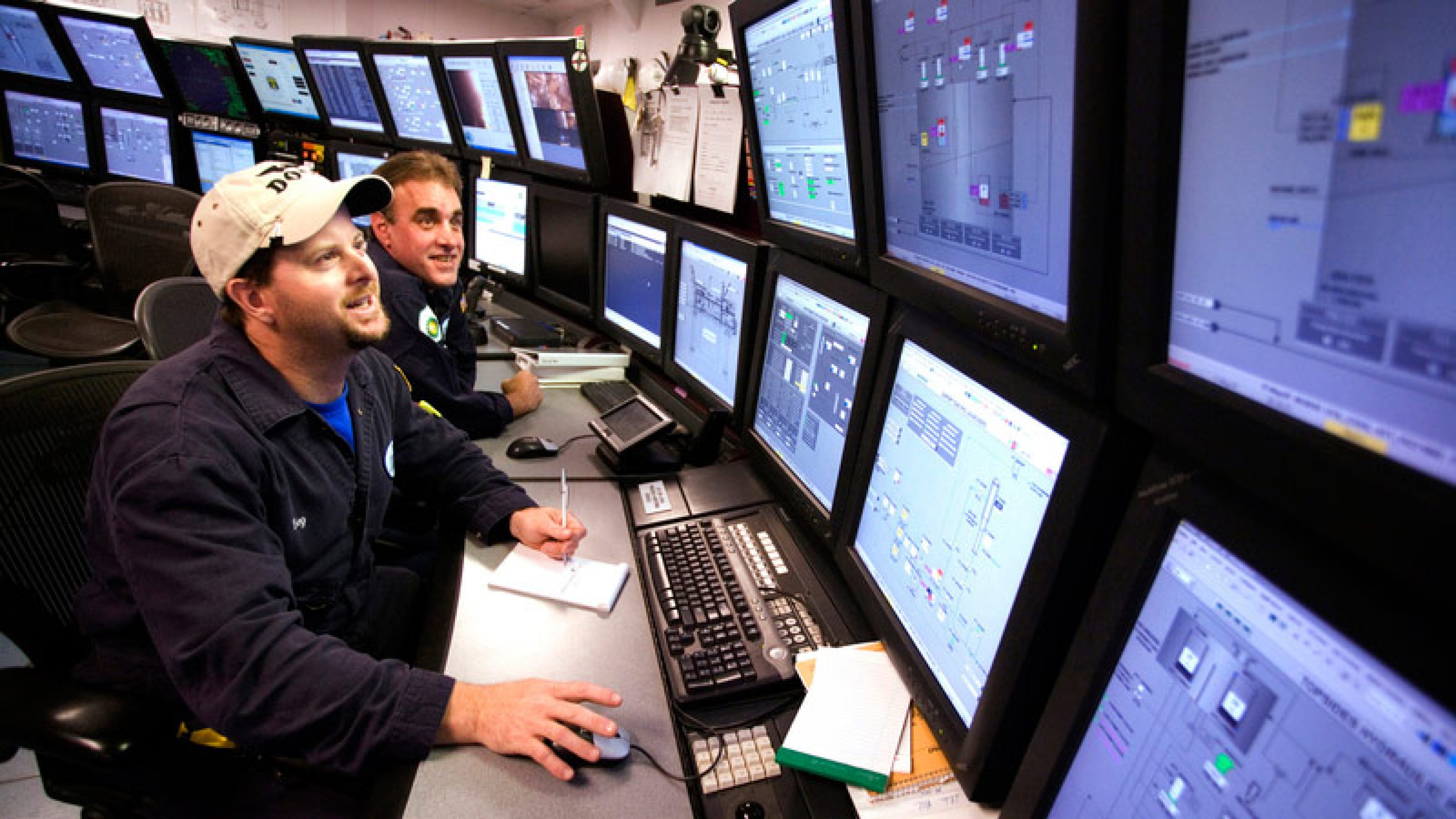 Technicians looking at mulitple screens displaying detailed information in the control room of the Atlantis platform in the Gulf of Mexico, USA