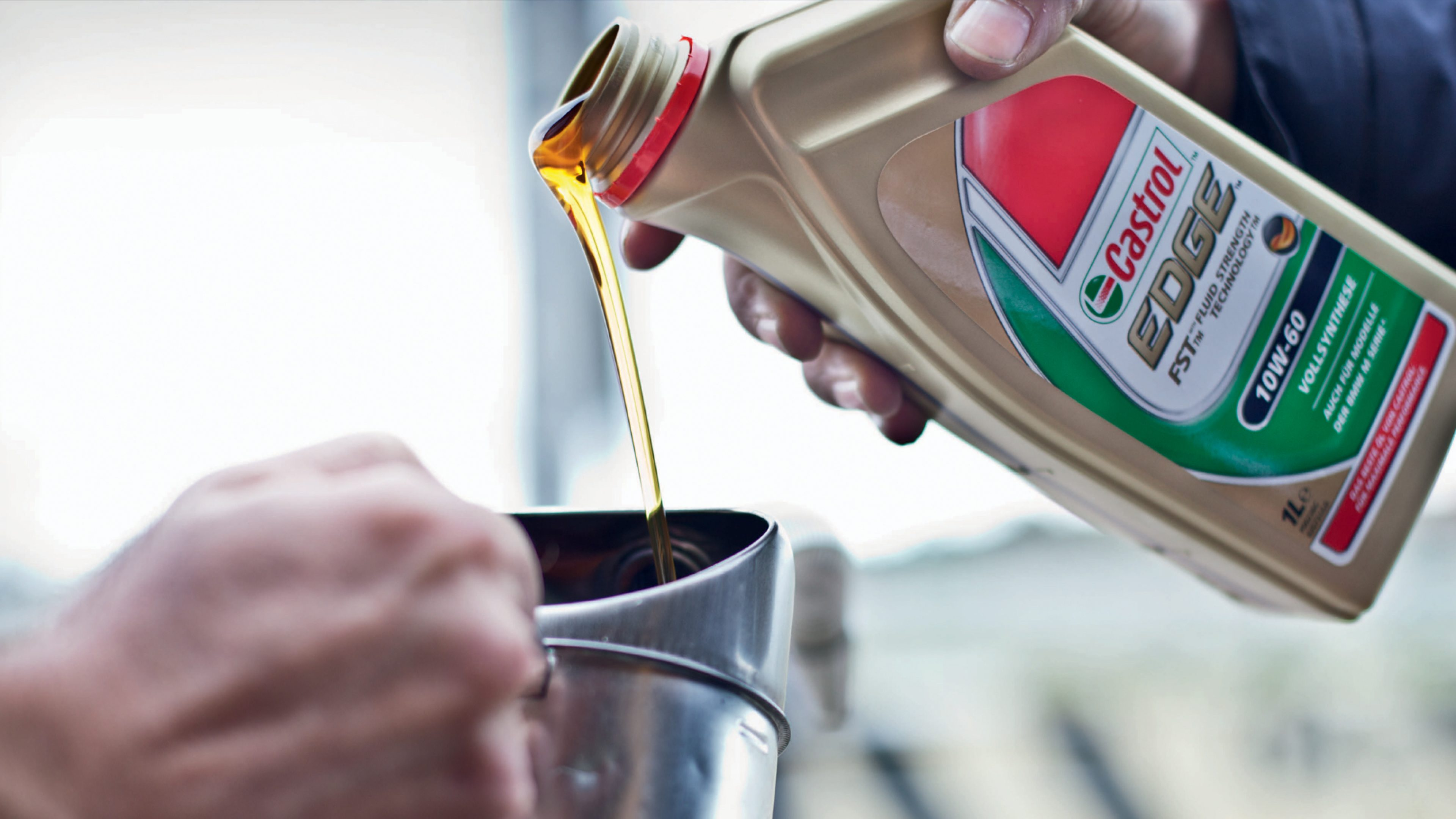 Castrol Edge lubricant being poured from the bottle into a silver container
