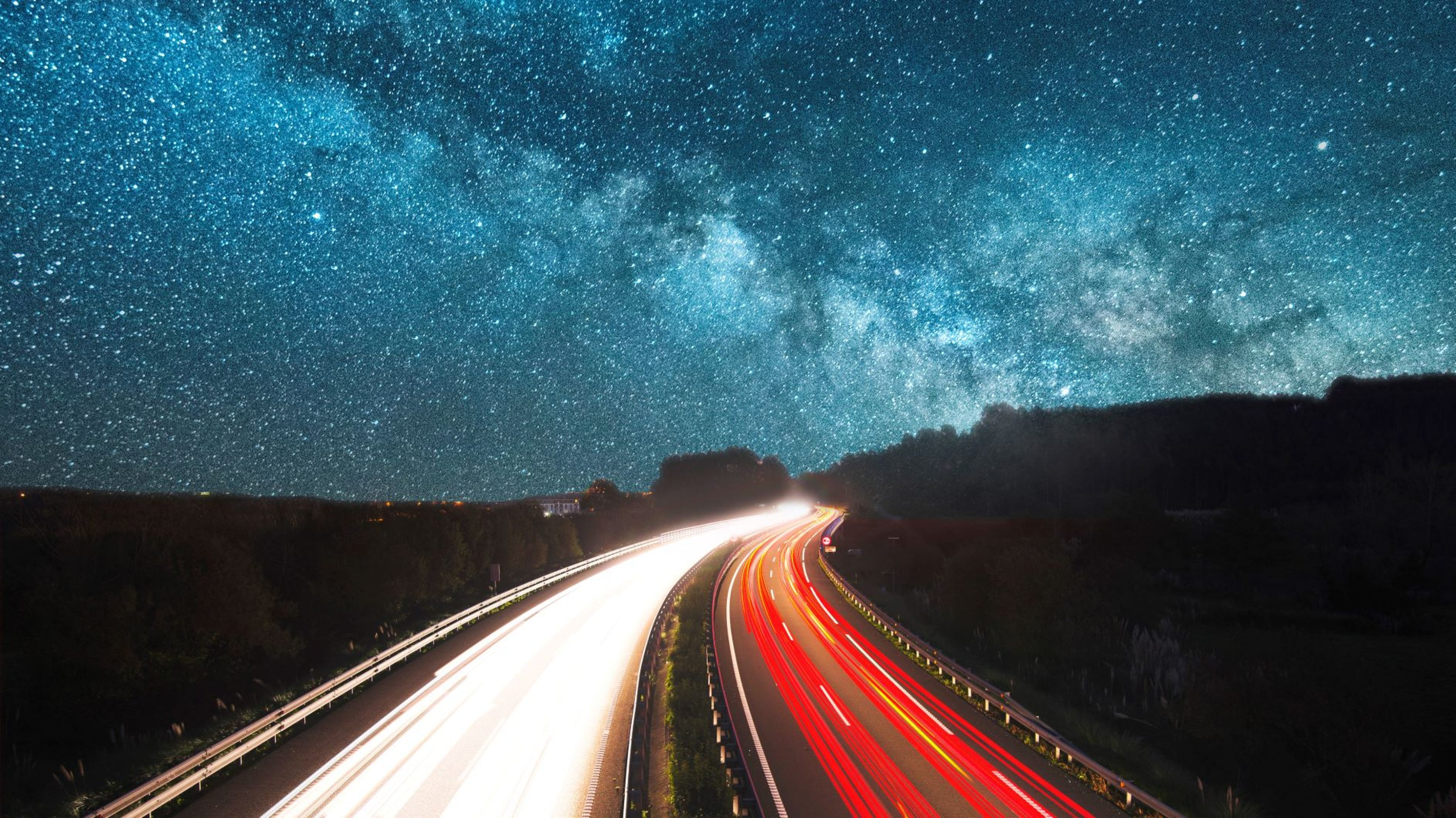 Time-lapse night-time view of a motorway beneath starry skies