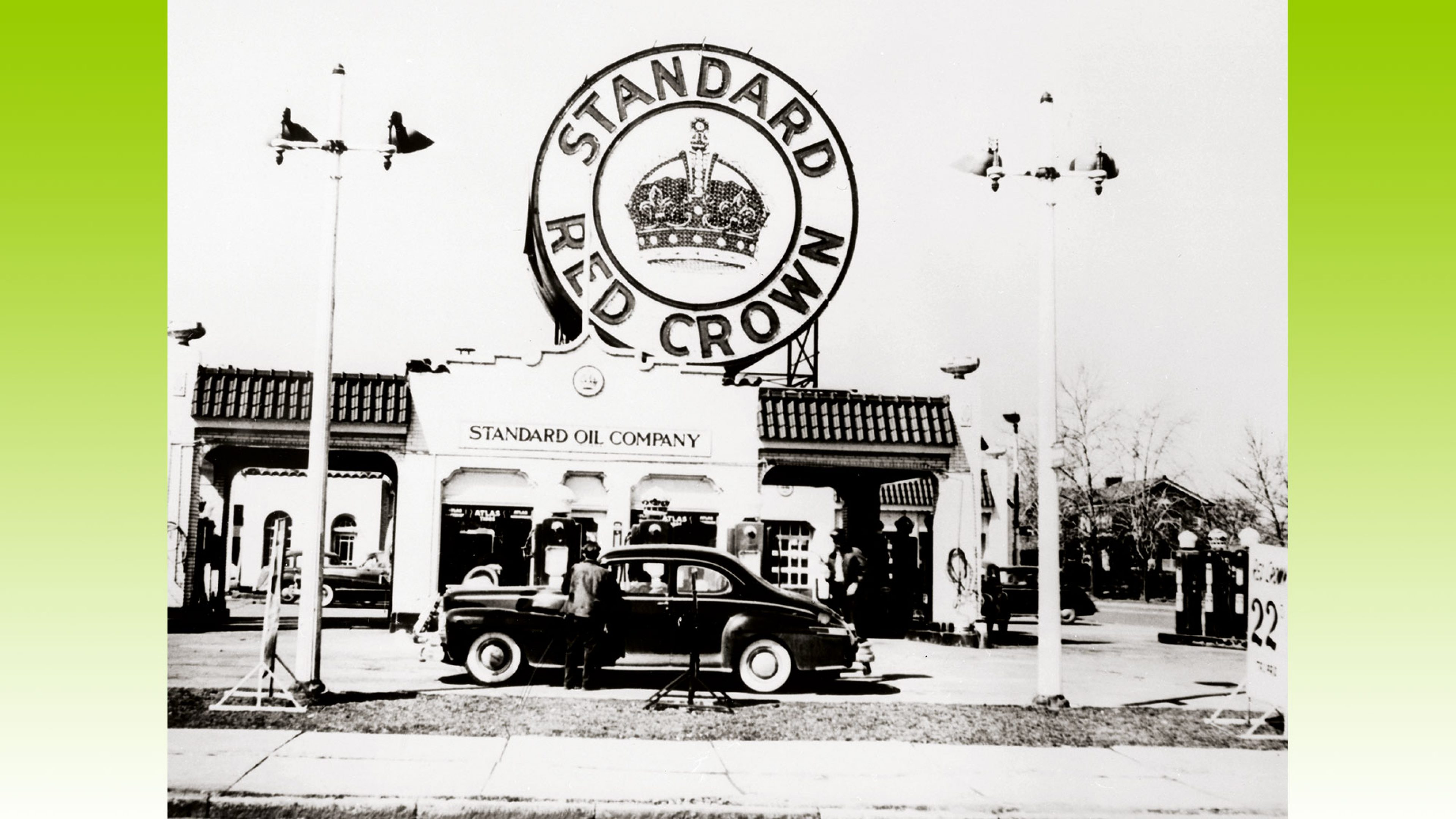 An early Standard Oil Company filling station. A huge sign, located on the roof of the service station, advertises Standard Red Crown gasoline
