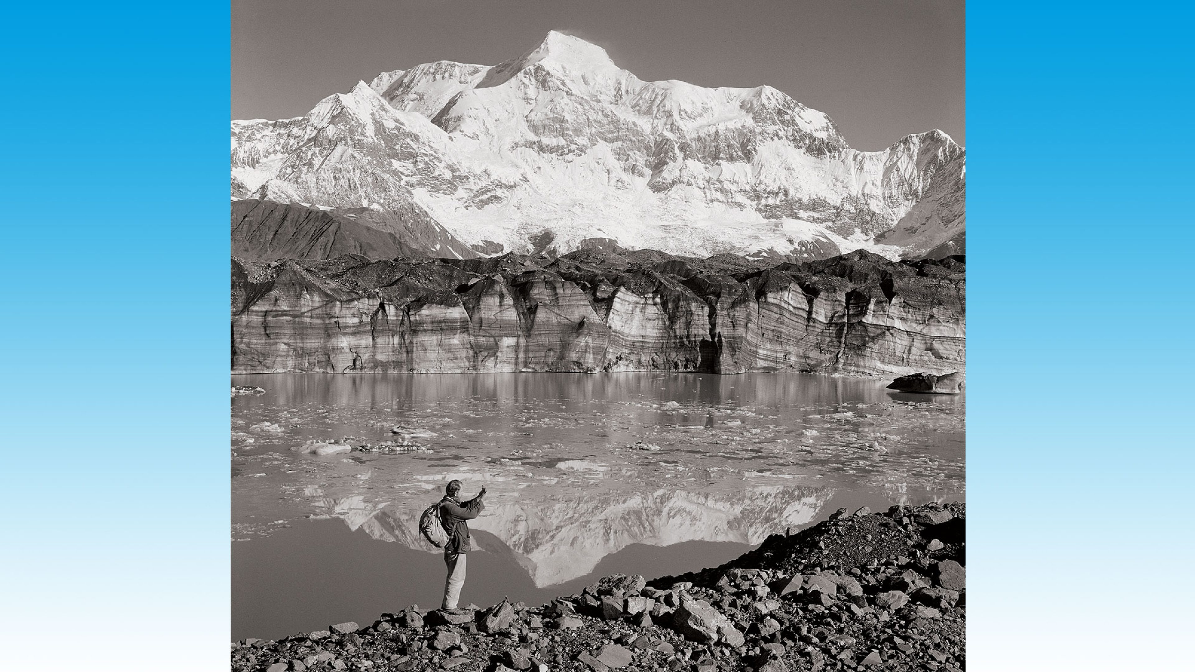 A BP explorer, standing by a glacial lake, while surveying in Alaska, 1961