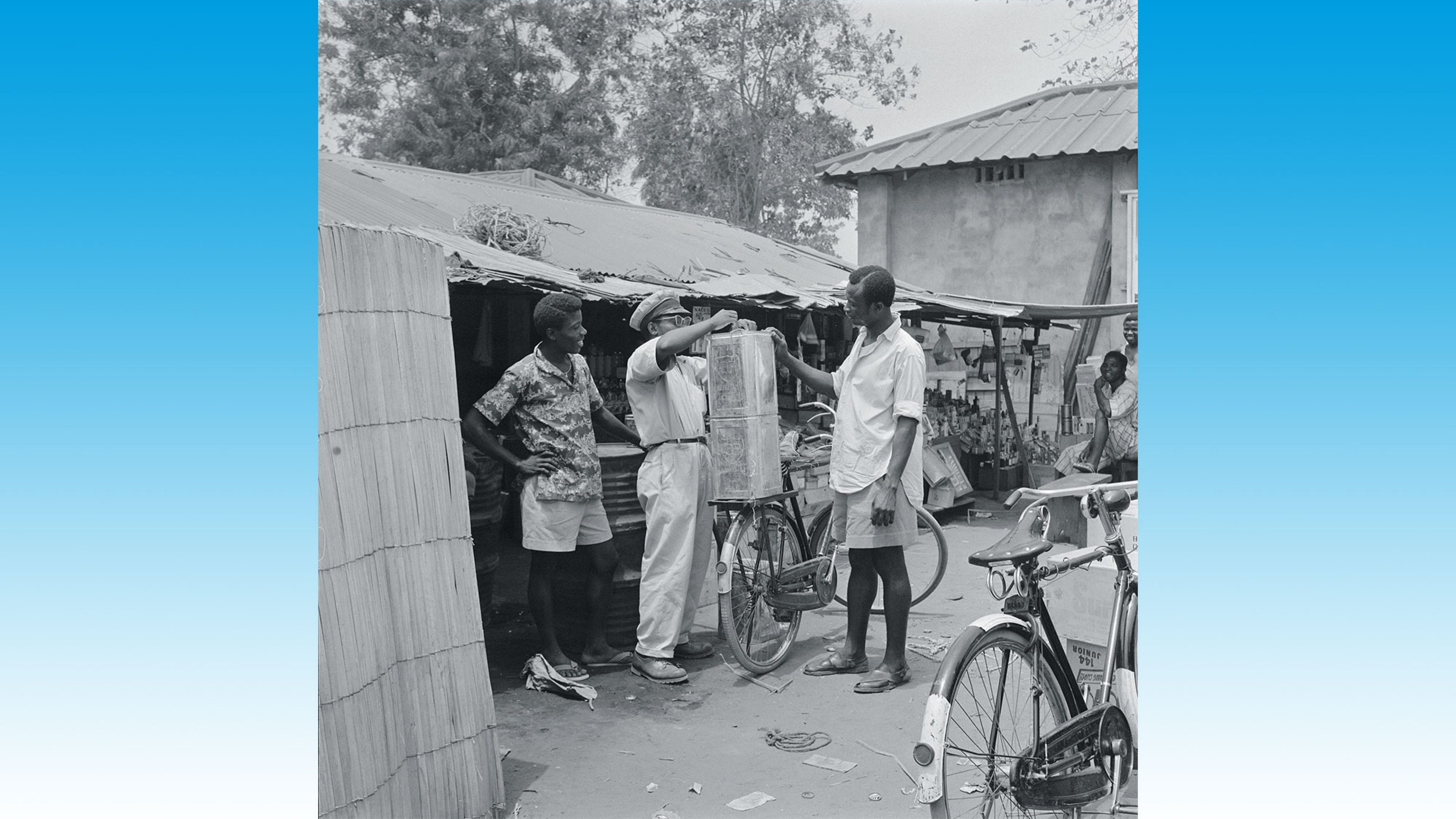 A BP kerosene stall at Port Harcourt's local market, Nigeria, 1961. A trader secures purchases onto the customer's bike