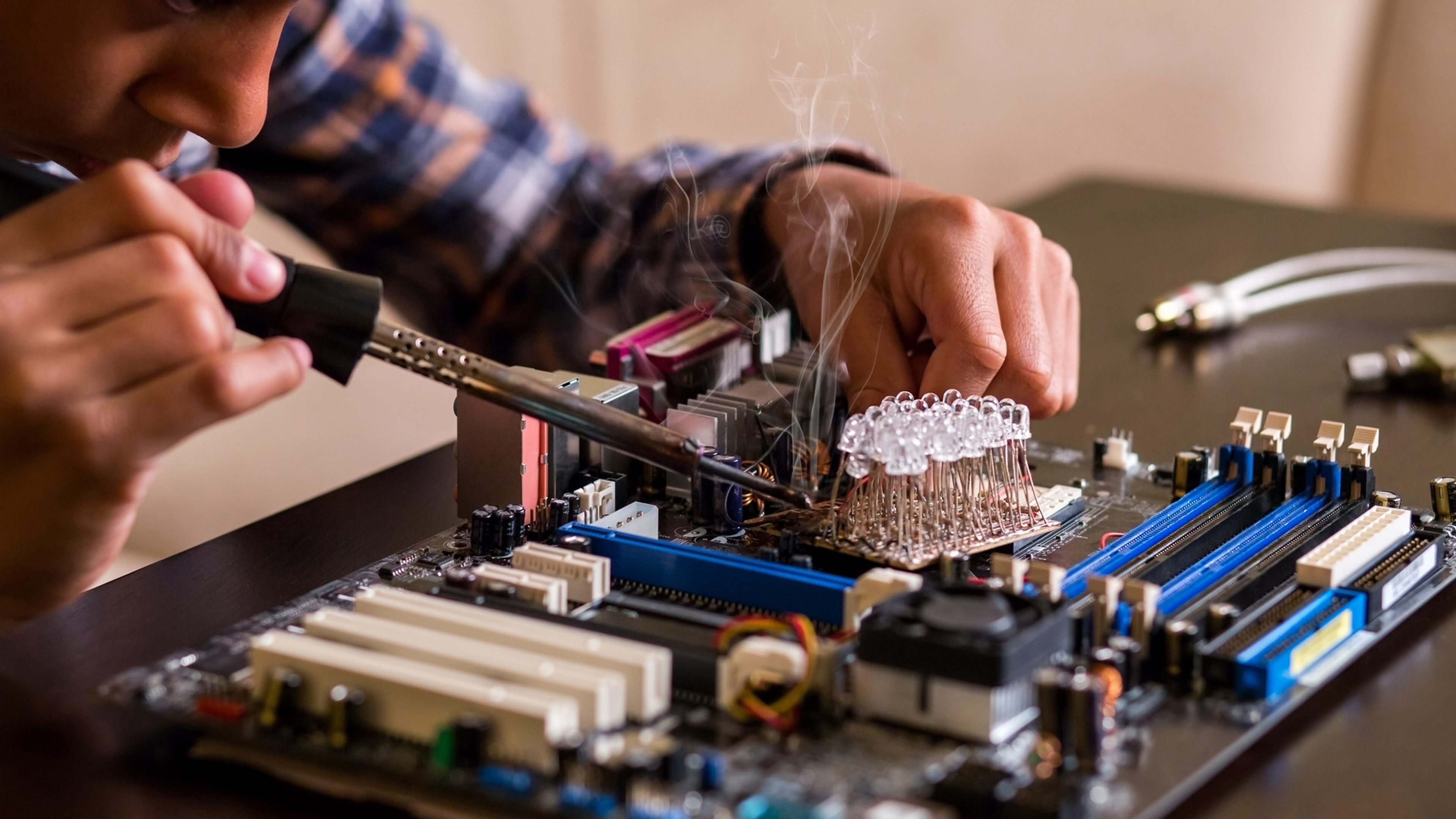 A male technician solders parts on a computer motherboard