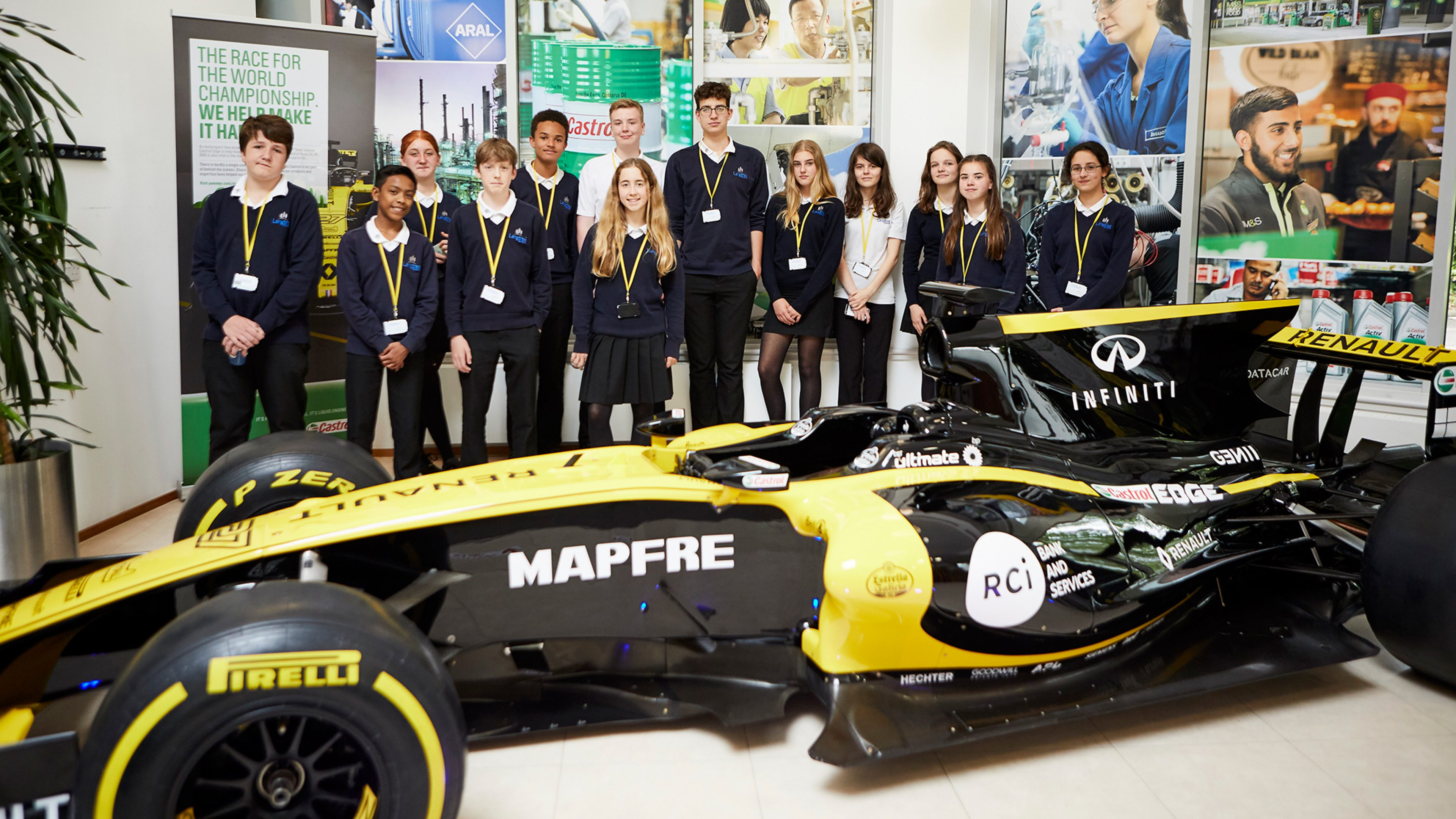 A group of secondary school girls and boys admire an F1 racing car