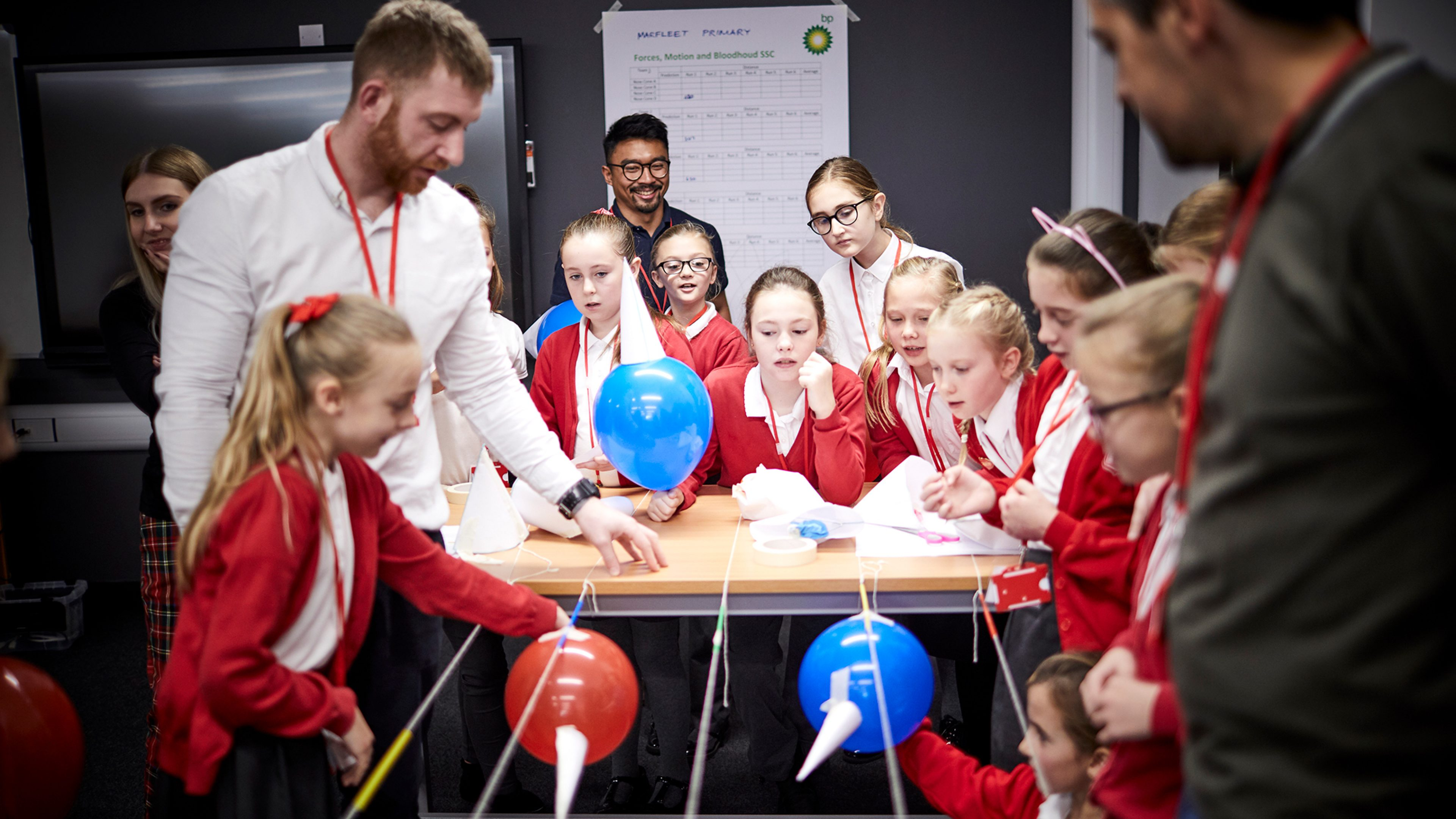 Primary school girls work with BP engineers to design an experiment