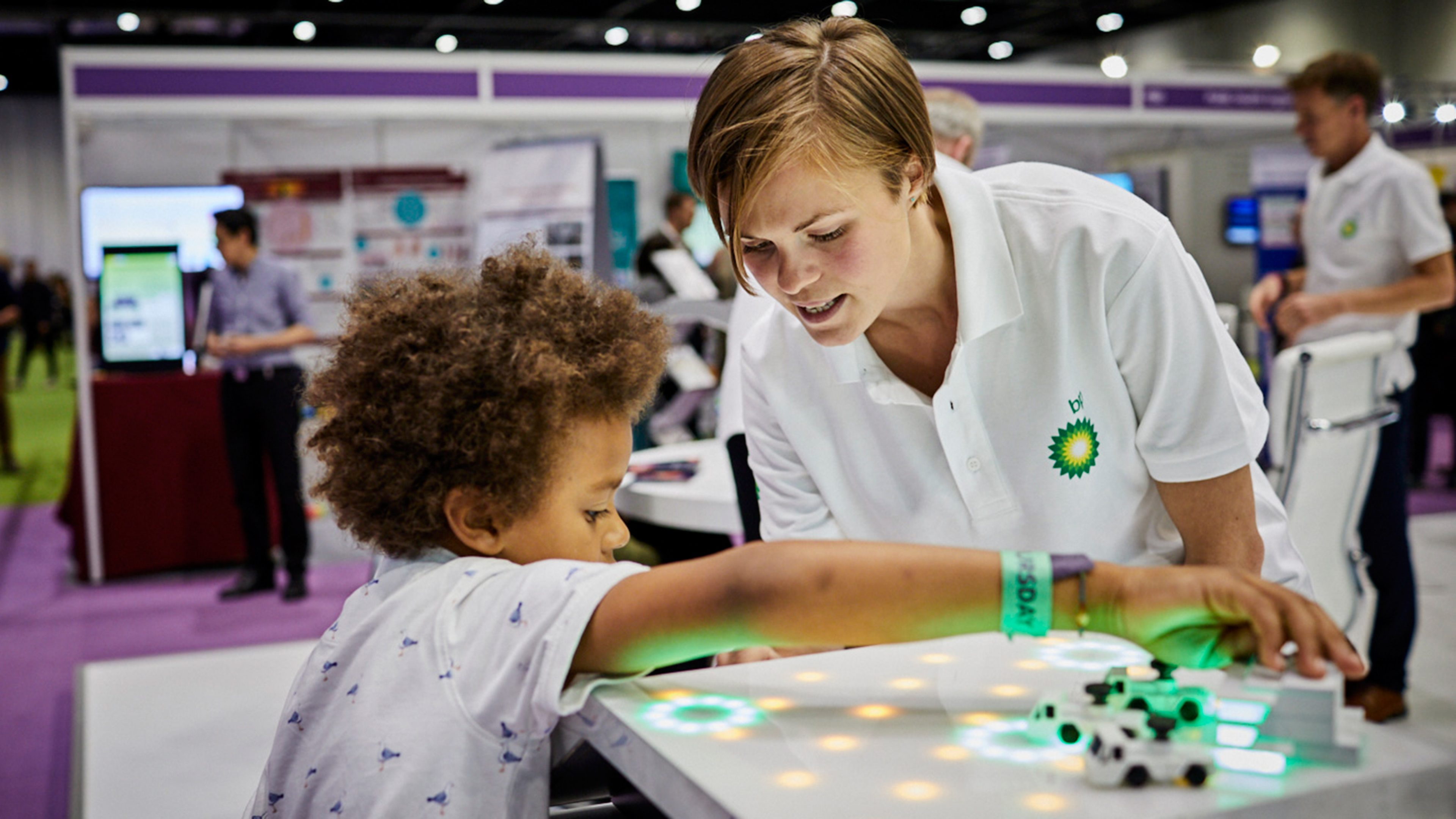 Woman in BP t-shirt showing child an engineering game