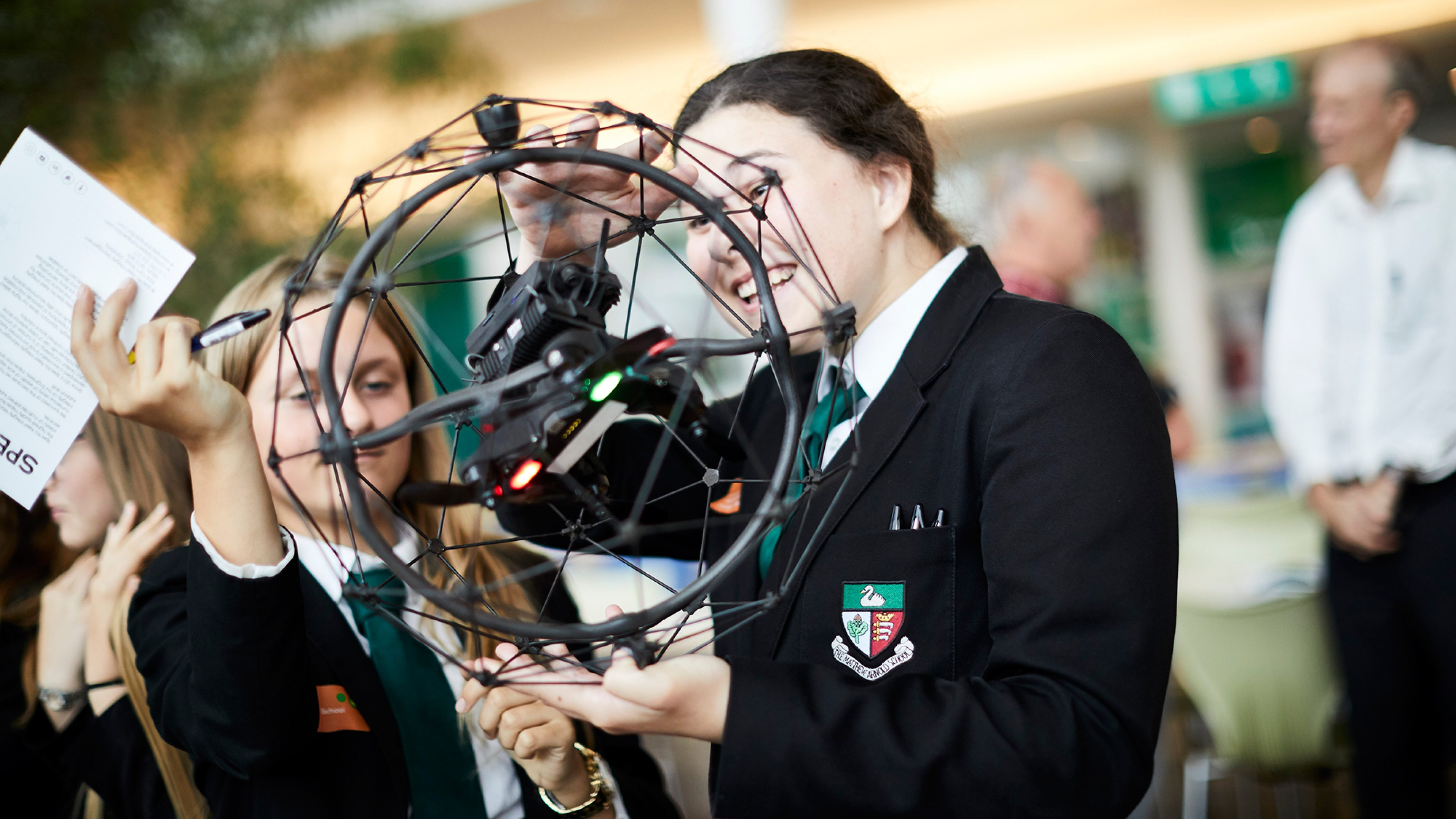 Two secondary school girls look at an engineering model
