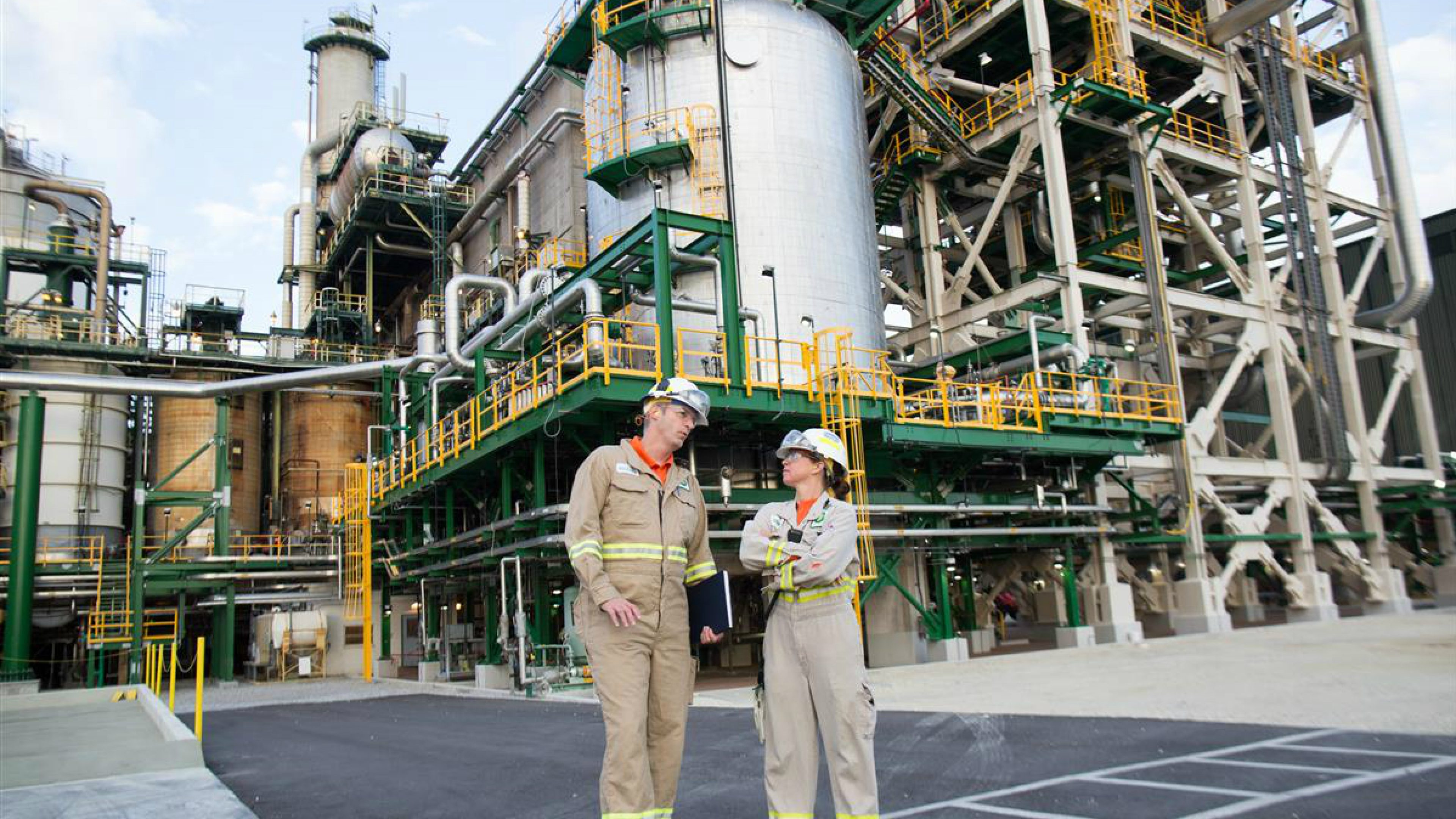 Two employees talking outside  refinery pipes