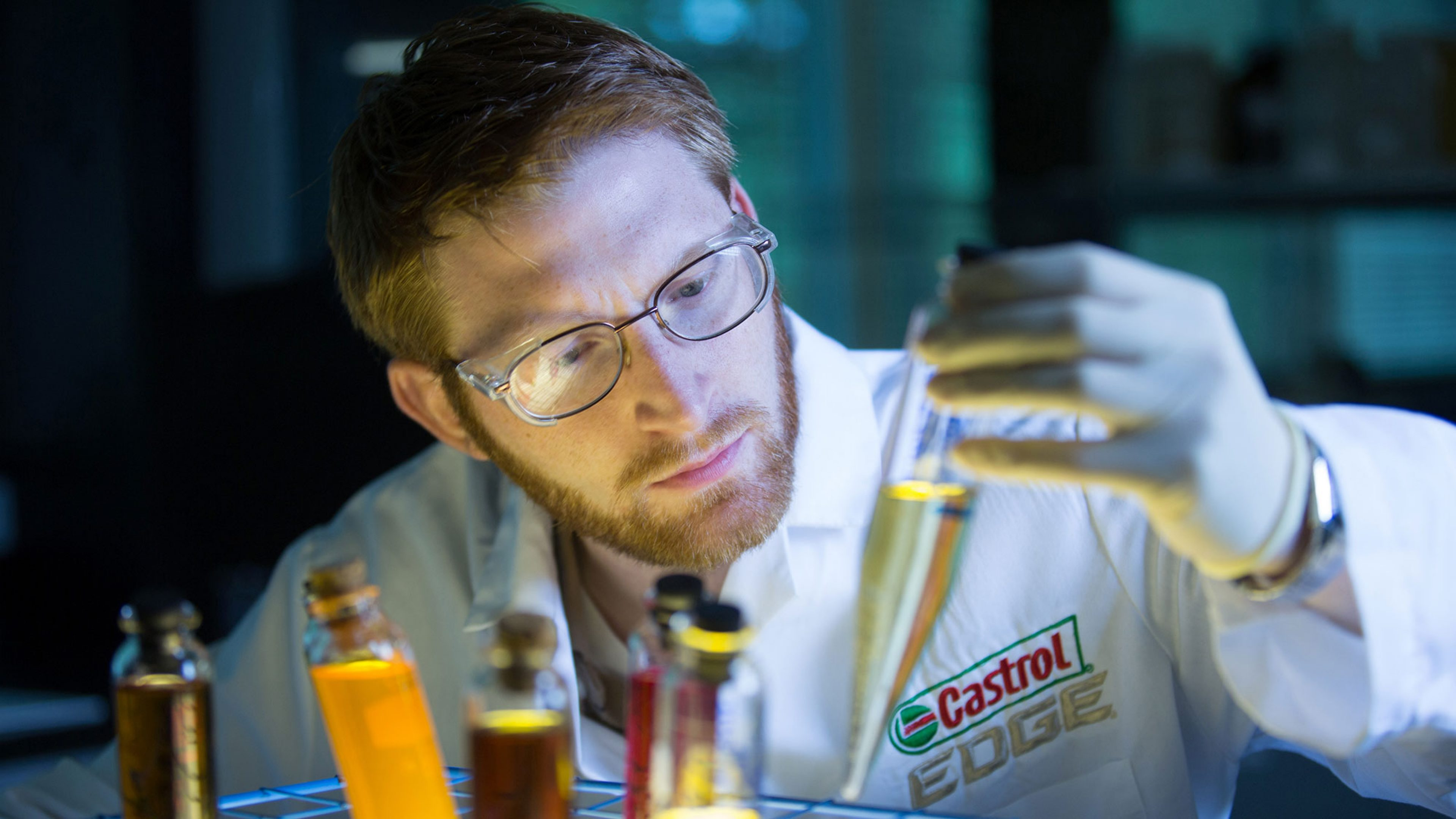 Employee looking at oil in glass tubes