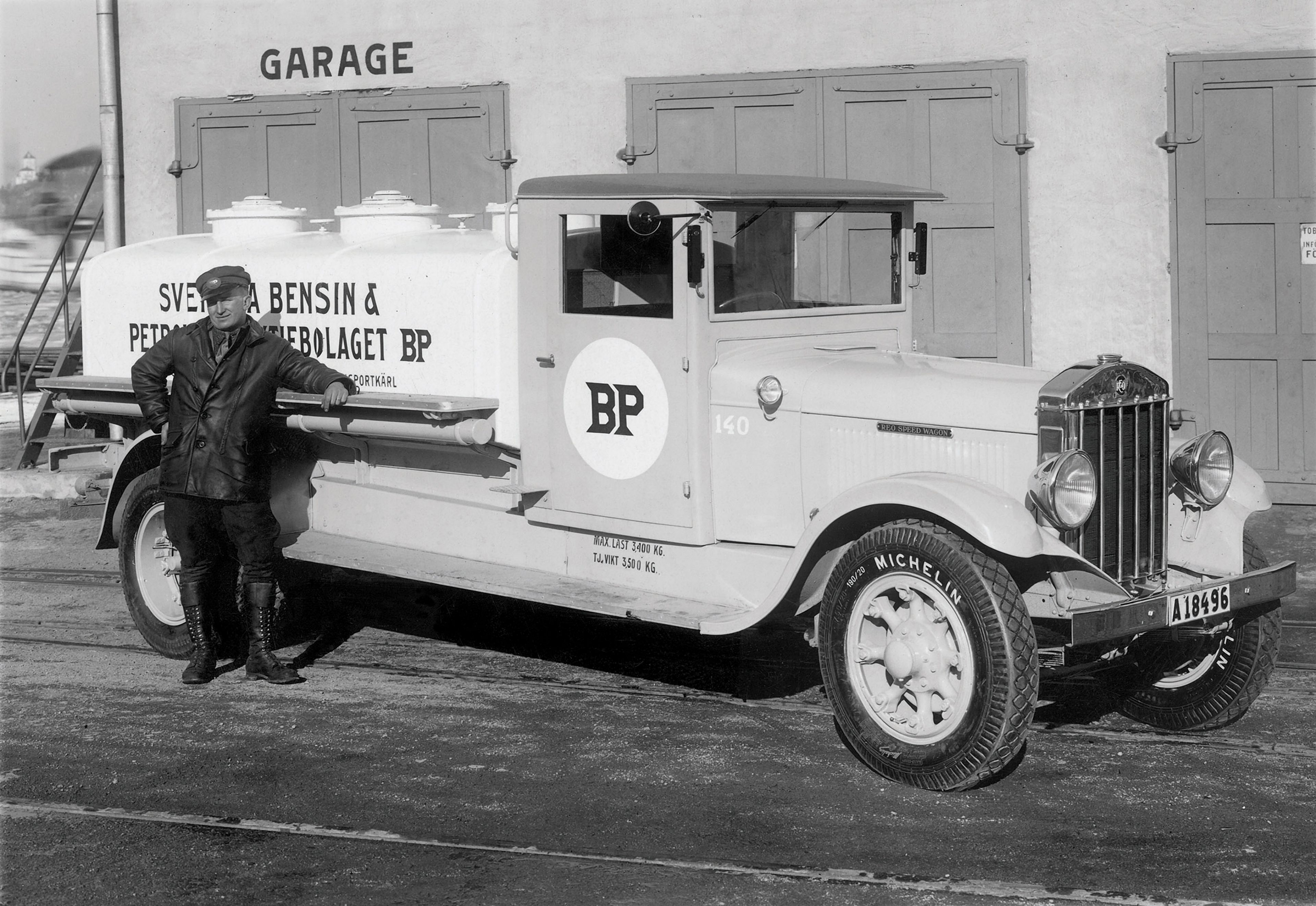 BP driver standing beside his delivery truck outside a garage. Motorised delivery vehicles of various shapes and sizes took over from horse-drawn tran...