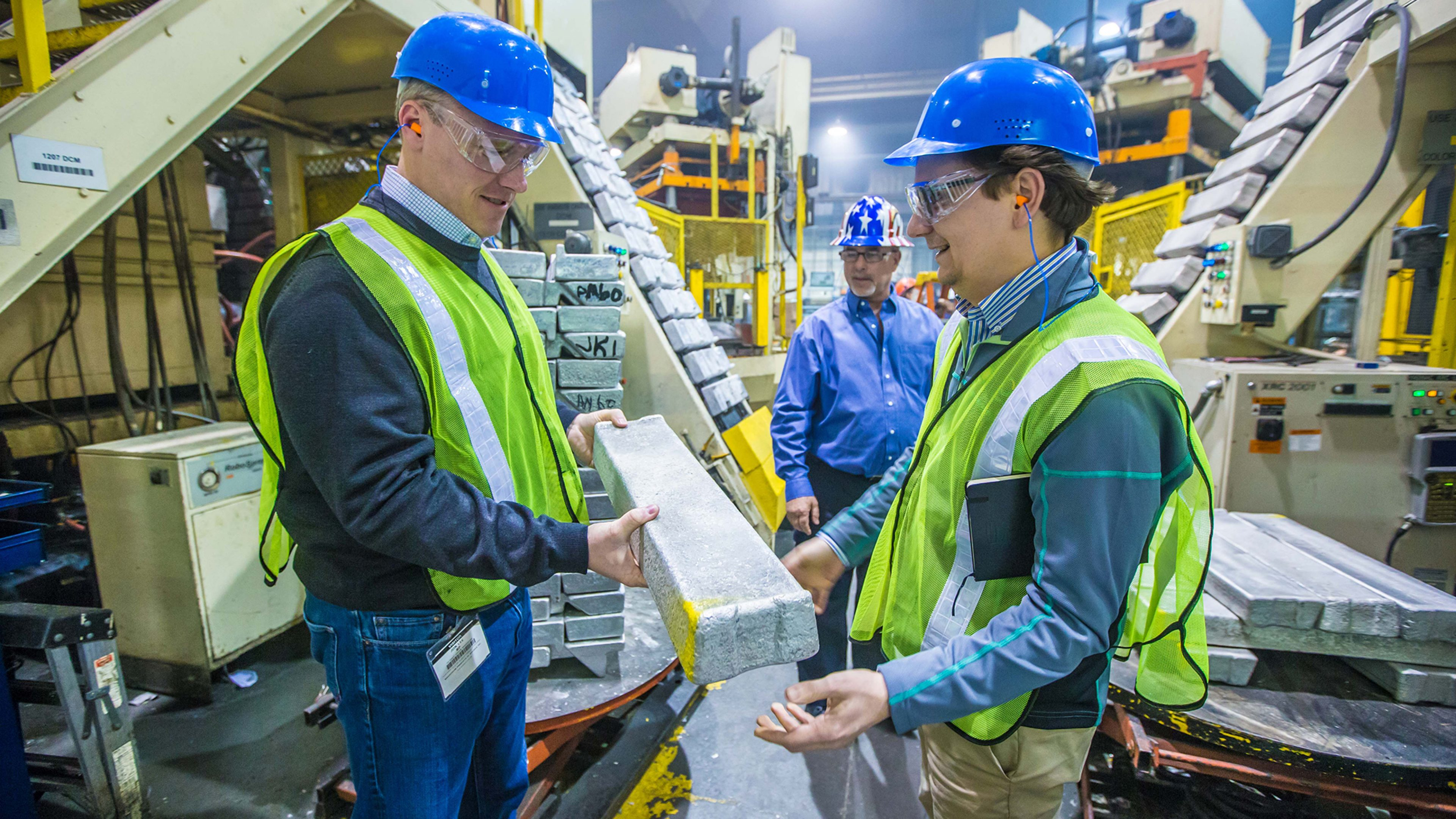 Two men in hard hats inspecting a magnesium ingot