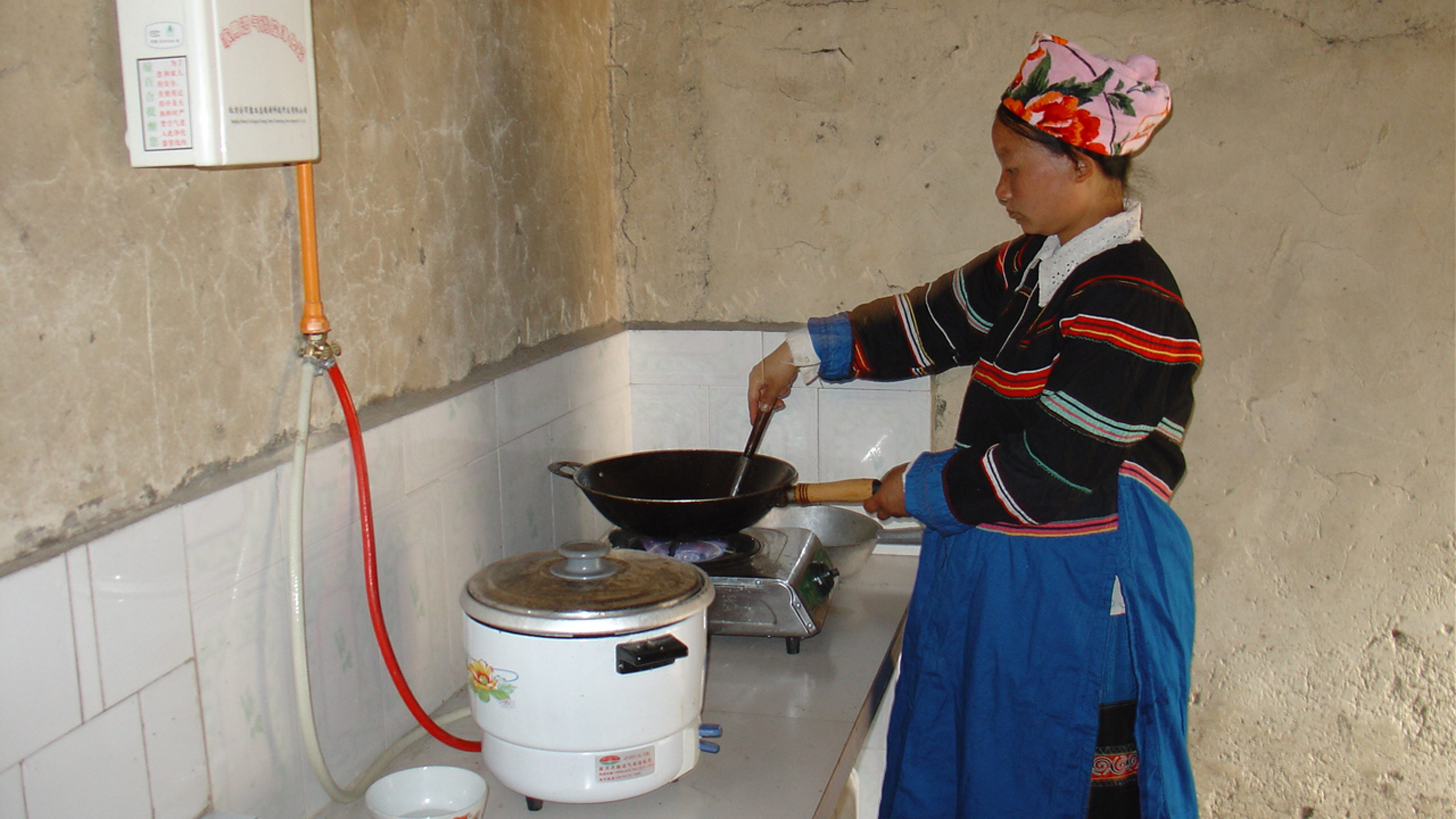 Reducing carbon, tackling poverty – biogas, China  – woman slow cooking and fried cooking using renewable biogas
