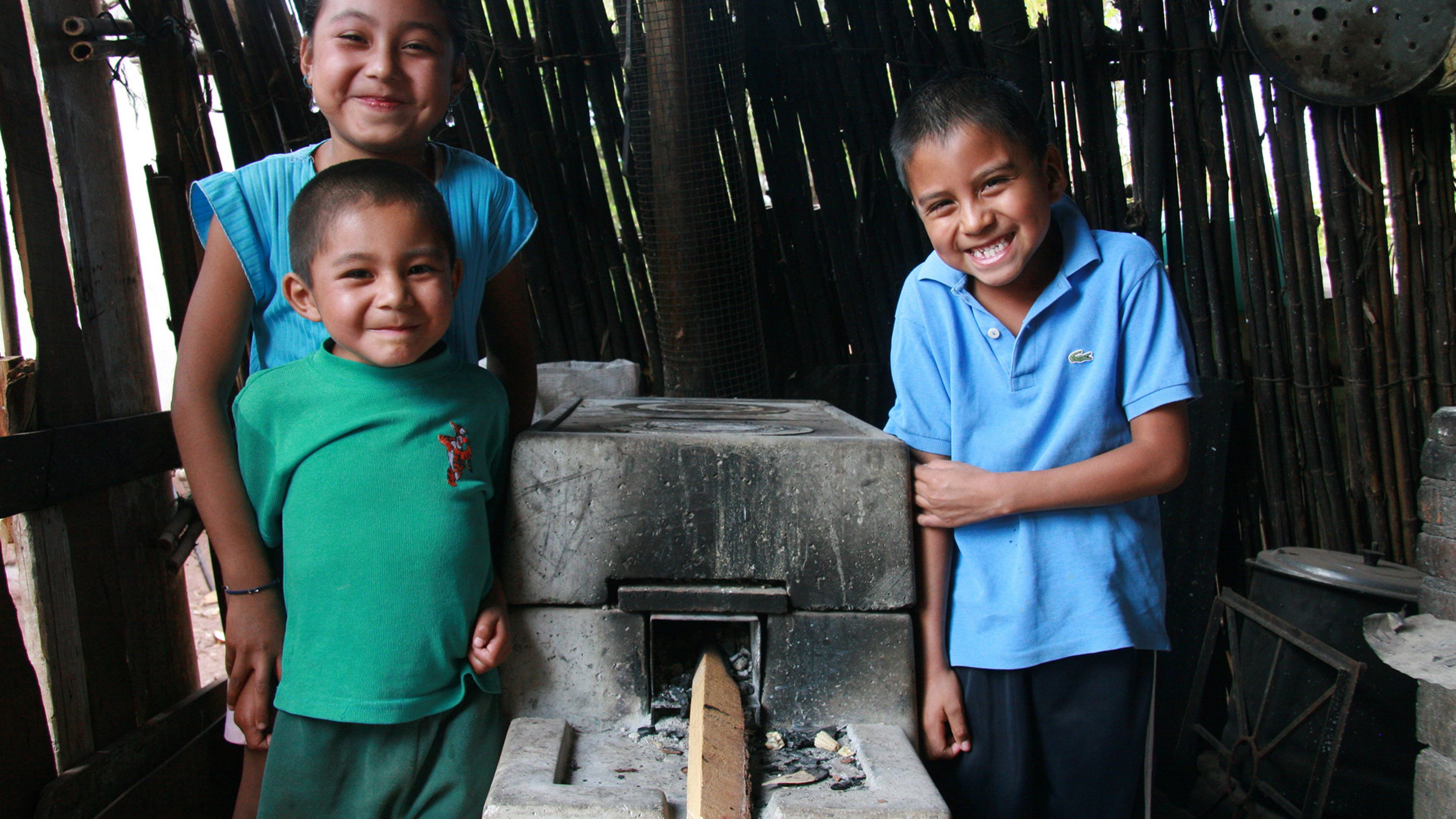 A young family gather round a newly installed ONIL cookstove from the ONIL cookstoves project, Mexico